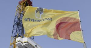A flag with the logo of Rosneft company flies next to an oil derrick at Suzunskoye oil field north from Krasnoyarsk, Russia. Photograph: Sergei Karpukhin