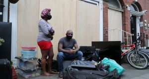 Theresa Chimamkpam and Elias Jegede with some of  their belongings outside the property on Berkeley Road in Dublin. Photograph: Nick Bradshaw