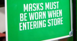 Sign advising customers at a store in Belfast to wear masks. Photograph: Liam McBurney/PA Wire