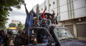 Malians climb onto a police vehicle and cheer as it drives through the streets of Bamako on Wednesday. Photograph: H Diakite/EPA