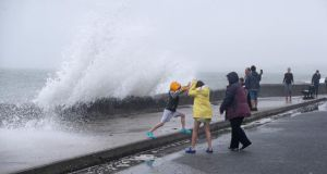 People are hit by waves on the Front Strand in Youghal, Co Cork on Wednesday. Photograph: Niall Carson/PA Wire
