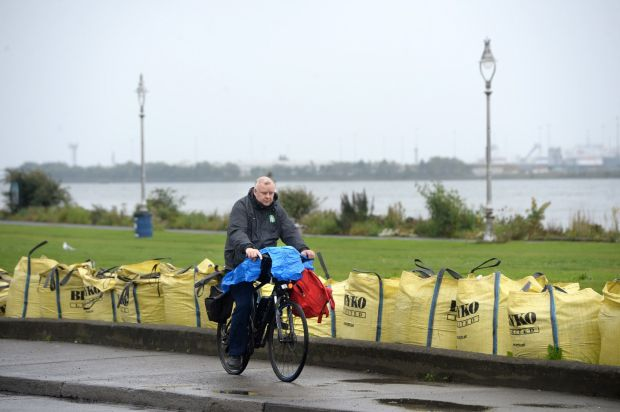 A man cycles past sandbags placed on the Clontarf Road in Dublin in preparation for storm Ellen. Photograph: Dara Mac Dónaill