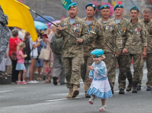 PLAYING SOLDIERS: A little girl marches along during a parade by Ukrainian veterans to mark Independence Day in downtown Kiev, Ukraine. Ukrainians are marking the 29th anniversary of their country's independence from the Soviet Union in 1991. Photograph: Sergey Dolzhenko/EPA