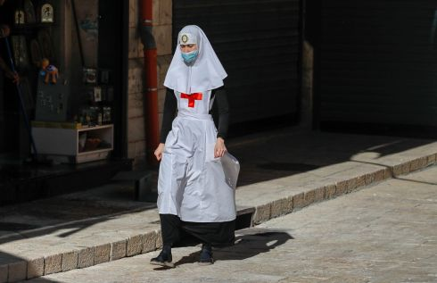 OLD CITY: A nun wearing a mask due to Covid-19 walks past shops on a deserted alley in the Old City of Jerusalem. Photograph: Ahmad Gharabli/AFP/Getty