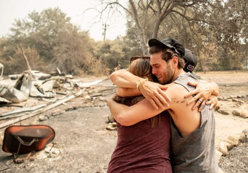 HOME DESTROYED: Austin Giannuzzi cries while embracing family members after viewing the burned remains of their home after a wildfire in Vacaville, California. Firefighters are battling some of California's largest-ever fires that have forced tens of thousands from their homes and burned one million acres of land. Photograph: Josh Edelson/AFP/Getty