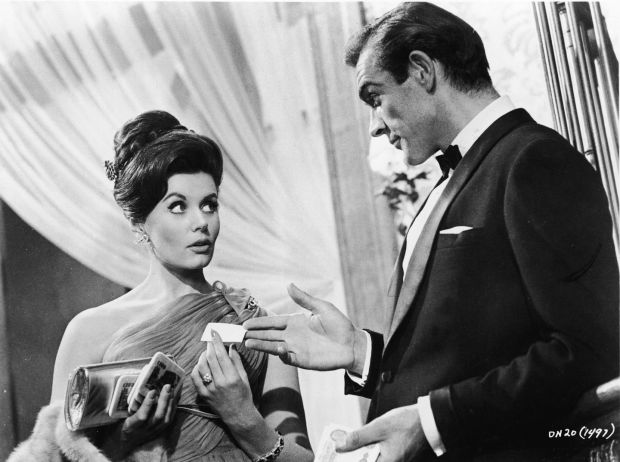 Scottish actor Sean Connery, as fictional secret agent James Bond, hands a business card to British actress Eunice Gayson in a scene from the film 'Dr. No,' directed by Terence Young, 1962. (Photo by MGM Studios/Courtesy of Getty Images) magazine