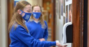 Transition year students wear face masks and use a hand sanitizer before entering a classroom on their first day back at school at Mount Sackville Secondary School in Chapelizod.  Photograph: Alan Betson/The Irish Times
