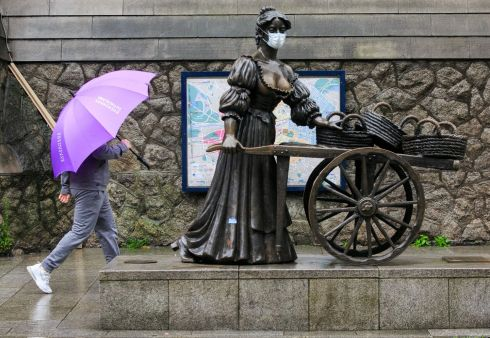 DOING HER BIT: Members of the public brave the bad weather while passing the Molly Malone statue on St Andrew's Street in Dublin's city centre. Photograph: Gareth Chaney/Collins