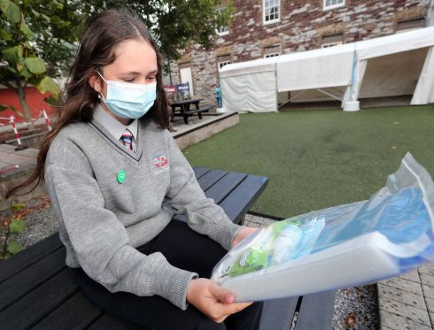 A FRESH START: Eve Ní Earchaí, a first-year student at Coláiste Daibhéid in Cork, inspects the Cork ETB Covid-19 starter pack. Cork Education and Training Board is supplying every student with two disposable face masks, a face shield, hand sanitiser and anti-bacterial wet wipes. Photograph: Jim Coughlan