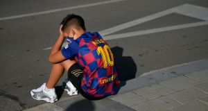 A child in a Lionel Messi jersey sits outside Barcelona's Ciutat Esportiva Joan Gamper in Sant Joan Despi waiting for the arrival of players to undergo a medical test for Covid-19. Photograph: Pau Barrena/Getty/AFP
