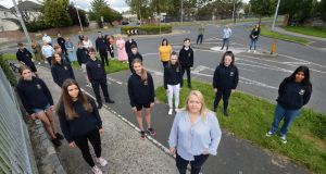 Liz Wynne of Confey College's parents council (front) alongside children and parents from the school, pictured in Lucan, Co Dublin. They fear the private bus which transports up to 200 children to the school will be axed. Photograph: Dara Mac Dónaill/The Irish Times