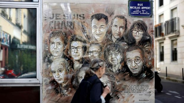 A woman walks past a painting by French street artist and painter Christian Guemy, known as C215, in tribute to staff of the Charlie Hebdo newspaper who were killed in the January 2015 assault, in Paris on August 31st, 2020. Photograph: Thomas Coex/AFP/Getty