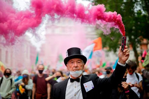 THEATRICAL FLARE: An Extinction Rebellion activist waves a flare during a climate change demonstation in central London, Britain. Photograph: Tolga Akmen/AFP via Getty Images