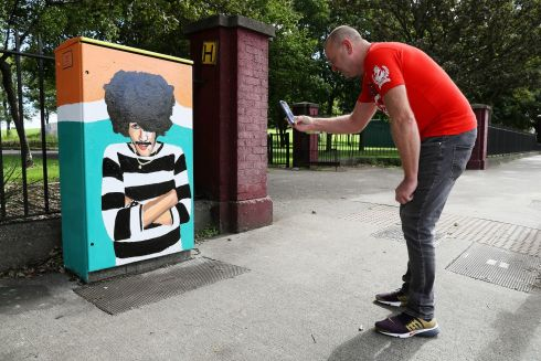 WAITING FOR A PASSERBY: Arthur Ayres stops to photograph a new mural of Thin Lizzy frontman Phil Lynott by artist Áine Macken, painted in Crumlin, Dublin. Photograph: Brian Lawless/PA Wire