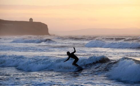 A surfer catches the last of the evening sun on Castlerock Beach, Co Derry with Mussenden Temple and Co Donegal in the background. Photograph: Michael Cooper