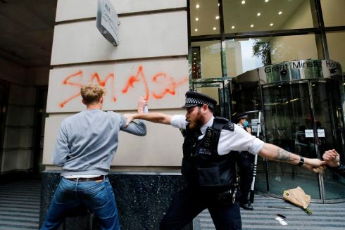 A police officer tries to stop an activist spraying graffiti on a wall during a demonstration against the HS2 high-speed rail line outside the Department for Transport, as part of protests by the Extinction Rebellion climate change group in central London. Photograph: Getty