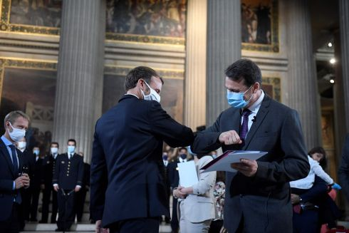 French president Emmanuel Macron elbow bumps after handing over a Welcome to French Citizenship booklet to a new French citizen during a ceremony to celebrate the 150th anniversary of the proclamation of the republic at the Pantheon, in Paris. Photograph: Julien De Rosa/AFP/Getty