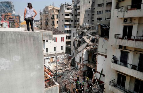 A woman looks on from a rooftop as rescue workers dig through the rubble of a badly damaged building in Lebanon's capital Beirut, in search of possible survivors. Photograph: Joseph Eid/AFP/Getty