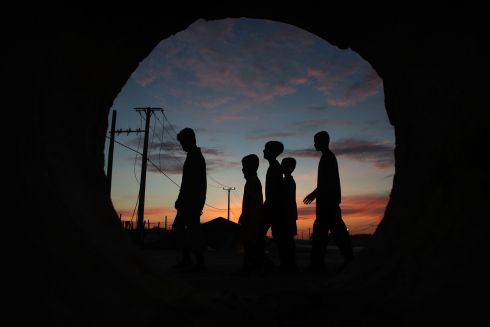 Boys silhouetted and seen through a sewage tube, after they offer food at a Buddhist pagoda during the Pchum Ben festival or Ancestors's Day in Kob Srov village on the outskirt of Phnom Penh, Cambodia. Photograph: Heng Sinith/AP