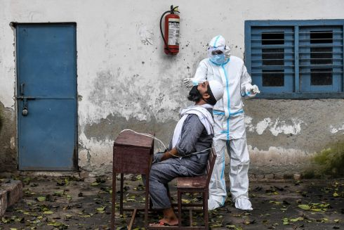 Medical staff take a sample from a man for a Rapid Antigen Test for Covid-19 at a temporary centre in a school in New Delhi. India passed four million reported cases of the virus on Saturday. Photograph: Prakash Singh/AFP/Getty