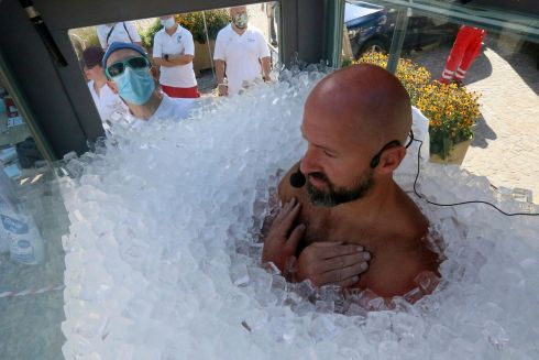 Austrian ice swimmer Josef Koeberl breaks his own world record of by standing in a glass cabin filled with ice for more than two hours, 30 minutes,  in Melk, Austria on Saturday. Photograph: Ronald Zak/AP