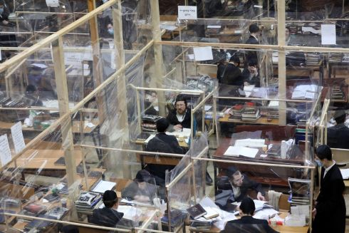 CORONAVIRUS: Ultra-Orthodox Jews study as they sit at plastic-separated capsule tables aimed at preventing infection with Covid-19, in Bnei Brak, Israel. Photograph: Abir Sultan/EPA