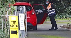 A motorist is handed a test kit at a pop-up Covid-19 testing facility in Dublin amid a spike in cases in the city. Photograph: Niall Carson/PA Wire