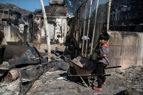 A migrant boy next to burned debris after a fire swept through the Moria refugee camp on the northeastern Aegean island of Lesbos, Greece, leaving more than 12,000 migrants in emergency need of shelter. Photograph: Petros Giannakouris/AP