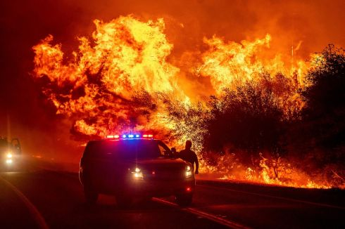 Flames lick above vehicles on highway 162 as the Bear Fire burns in Oroville, California., on Wednesday. The blaze expanded at a critical rate of spread as winds buffeted the region. Photograph: Noah Berger/AP