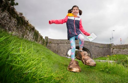 NATIONAL FAMINE WAY: Isobel Cullinan from Strokestown, Co Roscommon, at the launch of the new National Famine Way passport, guide and map beside the Royal Canal, in Cloondara, Co Longford. Isobel is wearing an oversized pair of bronzed shoes representing the 32 pairs of children's shoes placed along the National Famine Way from The National Famine Museum at Strokestown Park to Custom House Quay in Dublin. Photograph: Brian Farrell