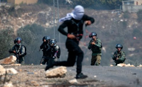 WEST BANK: A Palestinian protester runs as Israeli security forces advance in the village of Kfar Qaddum during clashes following a demonstration against Israel's plan to annex parts of the occupied West Bank. Photograph: Jaafar Ashtiyeh/AFP via Getty