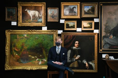 PICTURE PERFECT: An art dealer awaits customers at the Petworth Park Antiques and Fine Art Fair, at Petworth House in West Sussex. The fair has been postponed since May. Photograph: Kirsty O'Connor/PA Wire