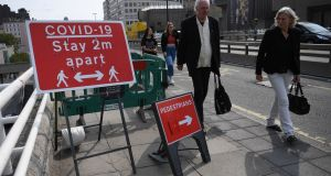 Pedestrians pass a social distancing sign on Waterloo Bridge in London, Britain, on Friday. Photograph: Neil Hall/EPA