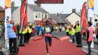 Mo Farah crossing the finish line after taking part in the Antrim Coast Half Marathon. Photograph: PA