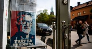 A sign with a portrait of Anders Tegnell, the face of the country's response to the novel coronavirus Covid-19 pandemic, is hanged at an entrance to a restaurant to instruct people to wash their hands in Sodermalm, Stockholm. Photograph: Jonathan Nackstrand/AFP