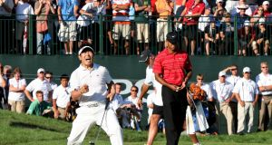 YE Yang of South Korea celebrates a birdie putt on the 18th green alongside Tiger Woods during the final round of the PGA Championship at Hazeltine National Golf Club in Chaska, Minnesota on August 16th, 2009. Photograph: David Cannon/Getty Images