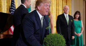 US president Donald Trump  picks up a bowl of shamrocks at  the White House in  2018. Photograph: Mandel Ngan/AFP