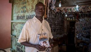 Felix Lutalo stands outside his music store in the bus park in Gulu, northern Uganda, holding a Westlife compilation he's selling. Photograph: Sally Hayden.