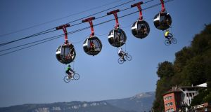 Cyclists hanging beneath the Grenoble Bastille cable cars during the 17th stage of the 107th edition of the Tour de France, 170km between Grenoble and Meribel. Photograph: Anne-Christine Poujoulat/AFP via Getty Images