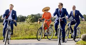 Dutch King Willem-Alexander (left) and Queen Maxima ride bicycles as they visit ECOstyle in Oosterwolde, The Netherlands.  Photograph: Koen Van Weel/EPA