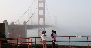 People and their children get a view of the Golden Gate Bridge through heavy haze in San Francisco, California on Monday. Photograph: John G Mabanglo/EPA