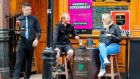 A worker serves a drink to customers sitting outside a pub in Dublin on Friday. Photograph: Paul Faith/AFP