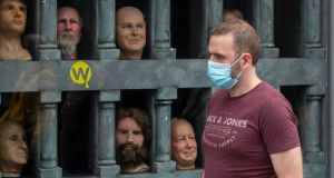 A man, wearing a protective facemask, passes the window of the Wax Museum, Dublin city centre, which remains closed due to Level 3 restrictions to tackle the spread of Covid-19 in Co Dublin. Photograph: Collins Photos