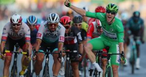 Sam Bennett celebrates winning the final stage of the Tour de France, and with it the green jersey. Photograph: Thibault Camus/Getty/AFP