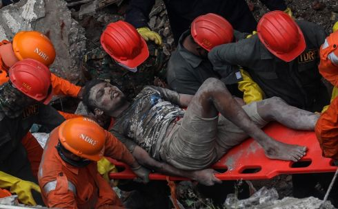 A SURVIVOR: National Disaster Response Force personnel rescue a survivor from the debris of a three-storey residential building which collapsed, in Bhiwandi, outskirts of Mumbai, India. According to reports, at least 10 people died and several were feared to be trapped under the rubble. Photograph: Divyakant Solanki/EPA