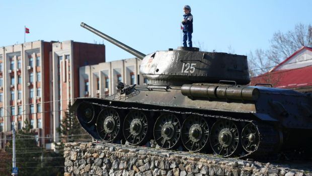A child stands on the T-34 Soviet tank set as a monument in the centre of Tiraspol. Photograph: Aleksey Filippov/AFP via Getty Images