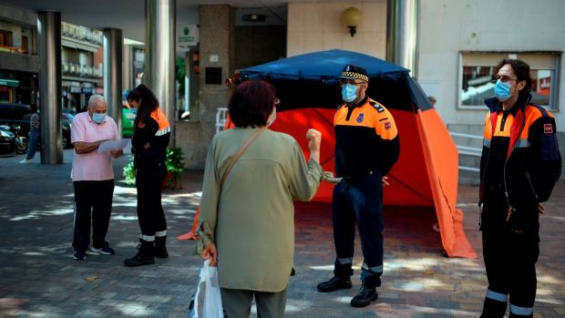Civil Defence members inform residents on the new restrictions imposed in the neighbourhood under partial lockdown of Usera, in Madrid, on Monday. Photograph: Oscar Del Pozo/AFP via Getty Images