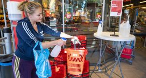A customer disinfects a shopping basket in Amsterdam, the Netherlands. Infections have surged in the Netherlands this month, with a new record of 2,245 infections detected in 24 hours this week in the country of 17 million. Photograph: Evert Elzinga/EPA