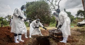 A team in protective gear carry out the burial of a coronavirus victim in Gulu, northern Uganda. Photograph: Sally Hayden