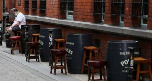 A man sits outside an empty pub in Dublin's city centre, where many shops and businesses are closed. Photograph: Brian Lawless/PA Wire